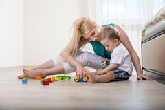 beautiful-young-mother-her-little-child-cheerful-mom-playing-kid-bedroom-boy-looking-toys-interest-his-mamma-56790011